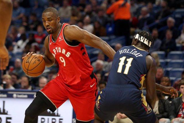 Serge Ibaka, de Toronto Raptors, ante Jrue Holiday, de New Orleans Pelicans