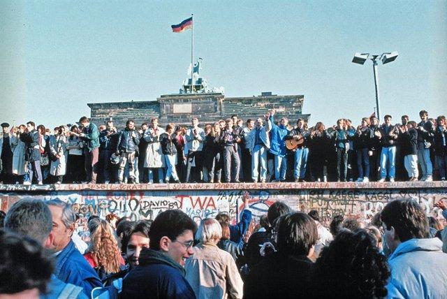 Los ciudadanos de la la República Federal de Alemania (RFA) y la República Democrática Alemana (RDA) celebran la caída del muro de Berlín frente a la Puerta de Brandeburgo, en Berlín (Alemania), a 9 de noviembre de 1989.