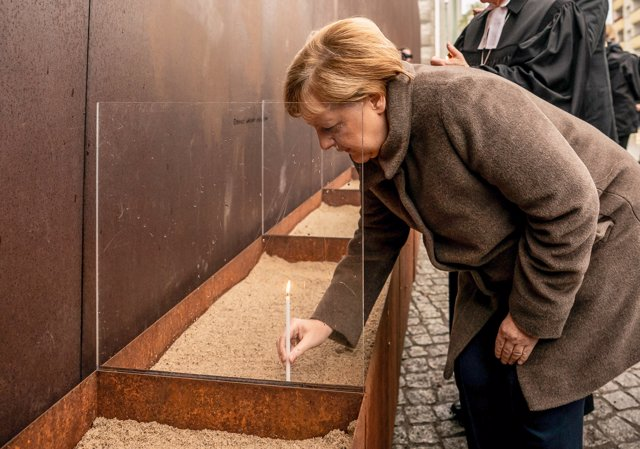 09 November 2019, Berlin: German Chancellor Angela Merkel, lights a candle in the sand at the Berlin Wall Memorial on Bernauer Street to mark the 30th anniversary of the fall of the Berlin Wall. Photo: Michael Kappeler/dpa