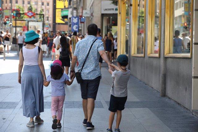 Una família passeja de la mà per un carrer de Madrid.