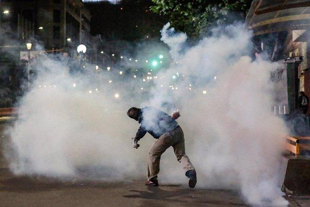 Un manifestante devuelve el bote de gases lacrimógenos lanzado por la Policía en una protesta en La Paz