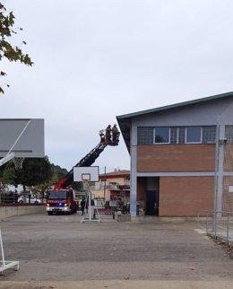 Els bombers retiren llaços grocs de la façana del Centre Cívic a la Cooperativa a Sarrià de Ter (Girona).