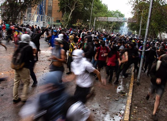 08 November 2019, Chile, Santiago: Protesters run during clashes with riot police following anti-government protest in Plaza Baquedano. Photo: Adrian Manzol/ZUMA Wire/dpa