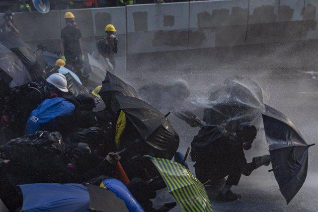Manifestants hongkonguesos davant dels canons d'aigua de la policia.