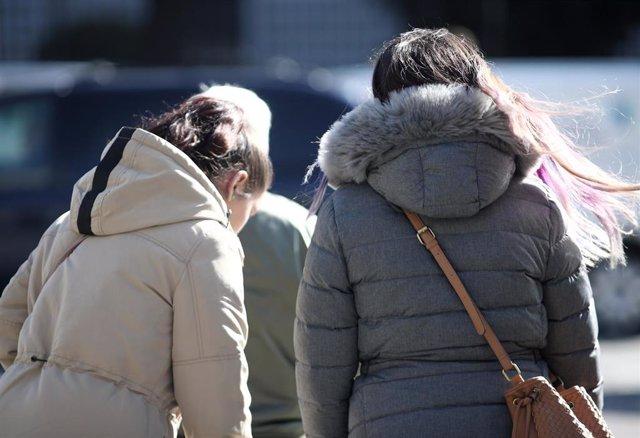 Dos mujeres con abrigo pasean en un día de viento por Madrid (España), a 8 de noviembre de 2019
