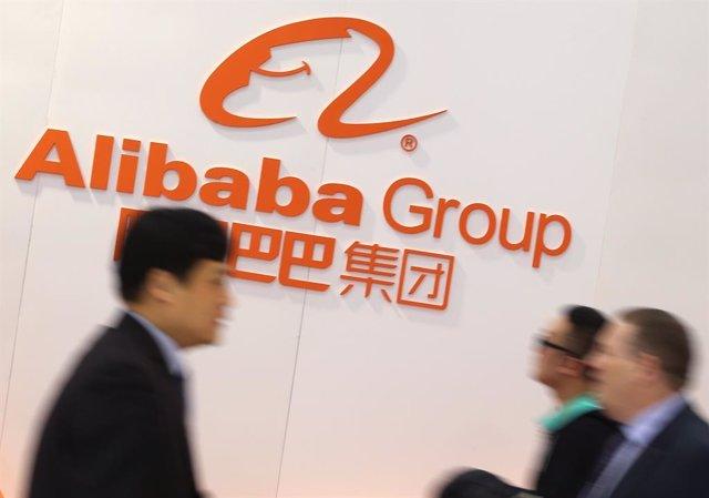 16 març del 2015: Persones passen per davant del logotip del grup d'Internet xinès Alibaba Grup durant l'inici de CeBIT. Foto: Christian Charisius/*dpa