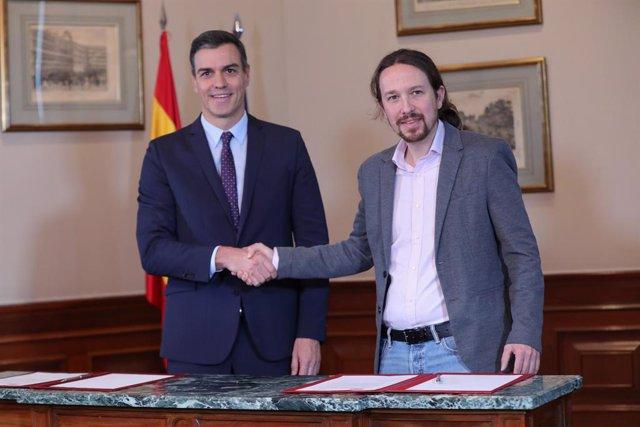 El president del Govern en funcions, Pedro Sánchez i el líder de Podem, Pablo Iglesias, s'encaixen la mà en el Congrés dels Diputats després de firmar el principi d'acord per a compartir un govern de coalició.