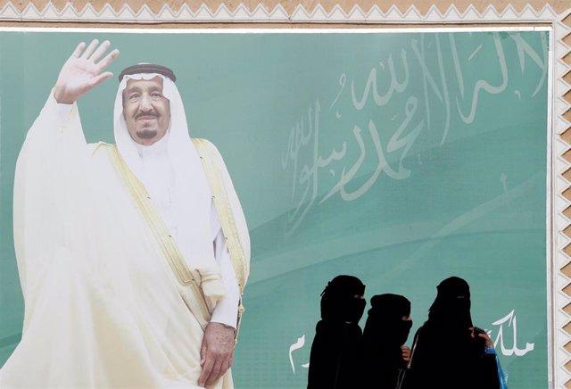 Mujeres ante un cartel del rey Salman de Arabia Saudí