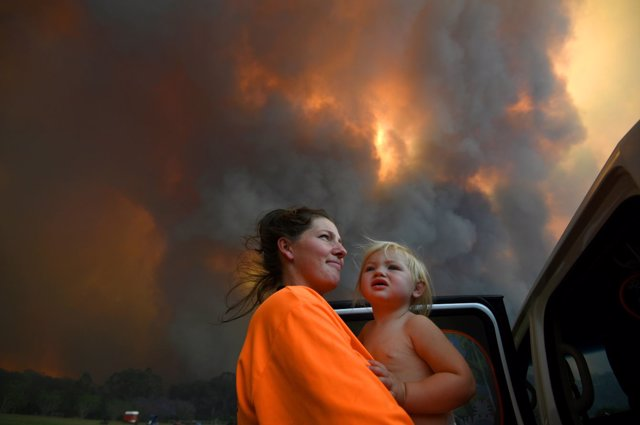 Sharnie Moren and her 18-month-old daughter Charlotte look on as thick smoke rises from bushfires near Nana Glen, near Coffs Harbour, Australia