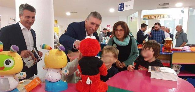El conseller Rafa Climent, en el centro, juega con tres niños durante la presentación de la Guía del Juguete de AIJU.