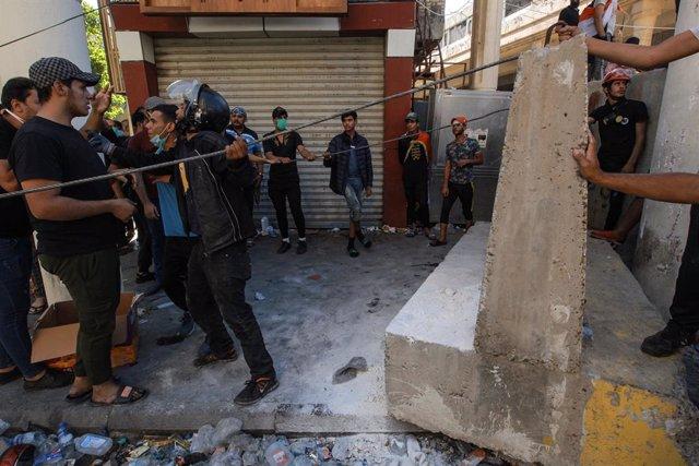 Agents de policia iraquians s'enfronten a manifestants a Bagdad.