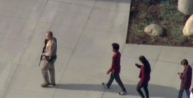 Un policía acompaña a estudiantes tras el tiroteo en el instituto Saugus de Santa Clarita, California.