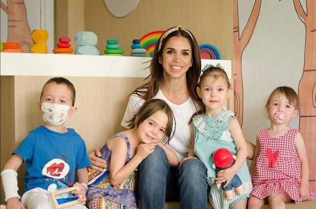 La actriz Elena Furiase posando junto a algunos de los niños de la Asociación NUPA.