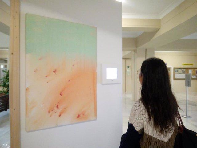 Alumna junto a una de las muestras de la exposición de Farmamundi