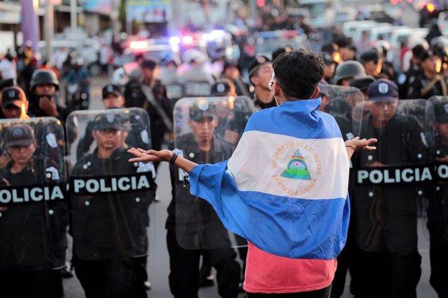 Manifestante antigubernamental delante de Policías antidisturbios en Managua