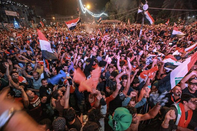 14 November 2019, Iraq, Baghdad: Iraqi protesters celebrate at Tahrir square after their national soccer team's 2-1 victory over Iran in the AFC 2022 FIFA World Cup qualifiers. Photo: Ameer Al Mohammedaw/dpa