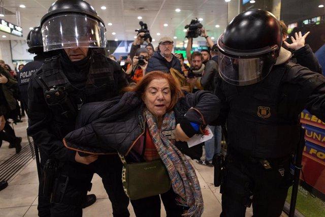 Los Mossos d'Esquadra sacan una a una a las personas que participan en la estación Barcelona Sants la sentada ante el vestíbulo de acceso a los AVE, convocadas por los CDR el 16 de noviembre de 2019
