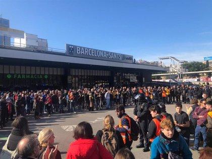 Los concentrados ante Barcelona Sants cantan 'Els Segadors' frente al cordón de Mossos