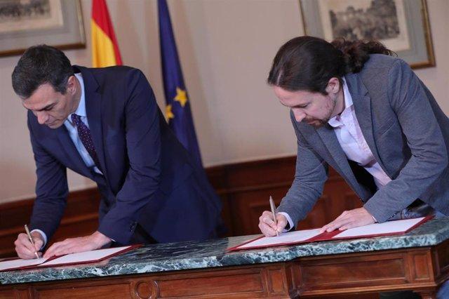 El presidente del Gobierno en funciones, Pedro Sánchez y el líder de Podemos, Pablo Iglesias, firmando en el Congreso el principio de acuerdo para compartir un gobierno de coalición.