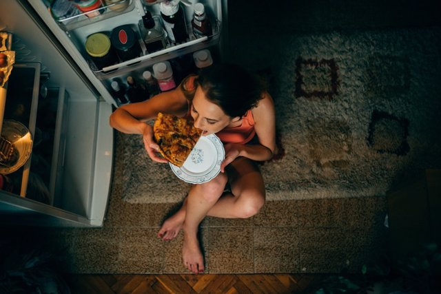 Woman eating in front of the refrigerator in the kitchen late night