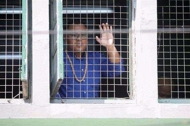 Paing Ye Thu, miembro de la compañía satírica Generación del Pavo Real, saluda a la prensa desde un tribunal de Rangún