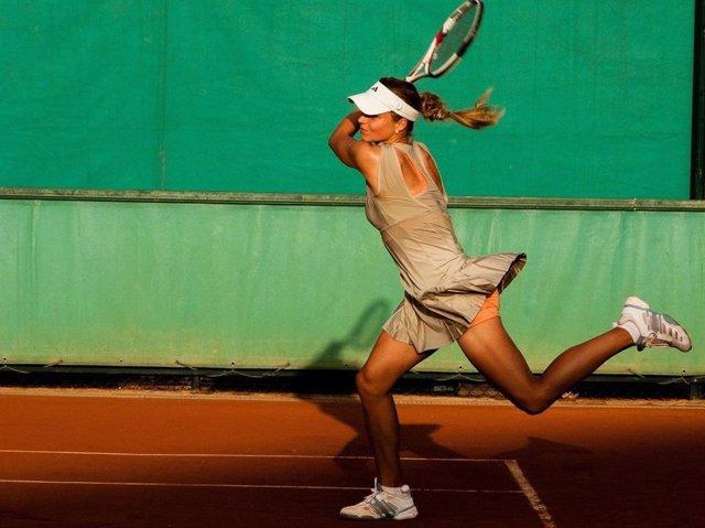 Mujer jugando al tenis.