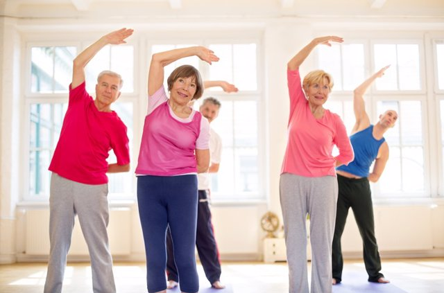 Senior people doing stretches together at gym