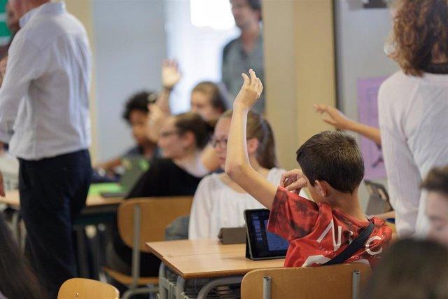 Un niño levanta la mano en un aula