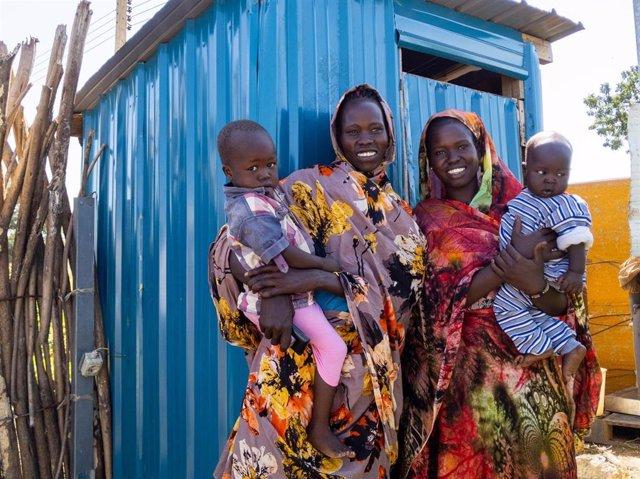 Theresa y Nyankyok con sus hijos frente a su letrina