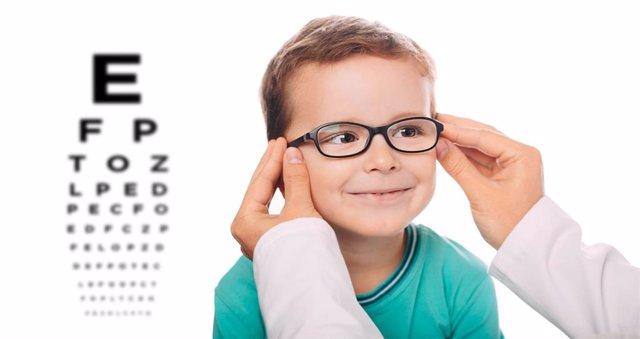 Oculista pone las gafas nuevas a un niño.