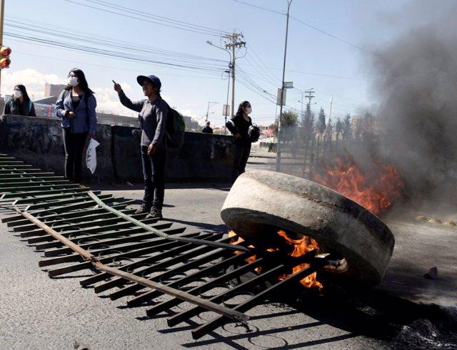 Pedestrians stand next to a blocked petrol plant of Senkata in El Alto outskirts of La Paz, Bolivia