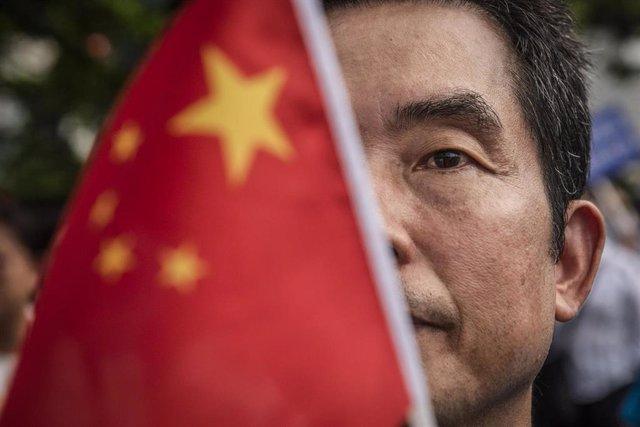 Un hombre sostiene la bandera china durante una manifestación (imagen de archivo)