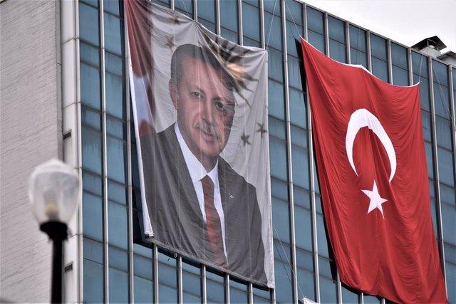 Retrato de Erdogan junto a una bandera de Turquía
