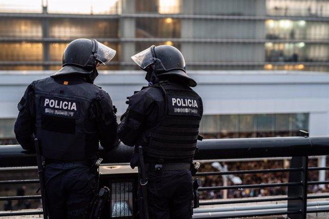 Dos agents dels Mossos de Esquadra a l'Aeroport de Barcelona-el Prat, on una multitud s'ha concentrat en protesta per la sentència del Tribunal Suprem sobre el judici del procés, a Barcelona (Espanya), 14 d'octubre del 2019.