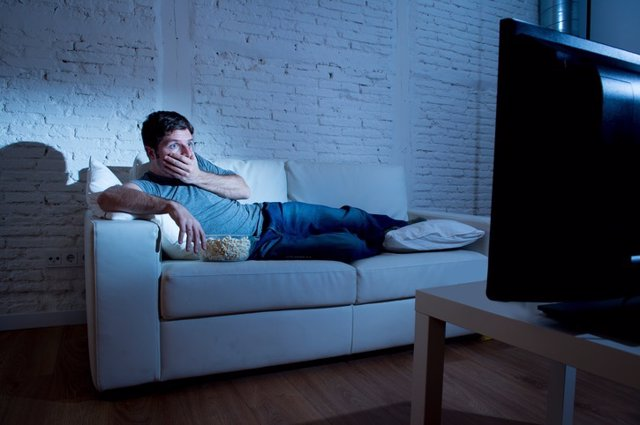Man watching television with remote control surprised disbelief face expression