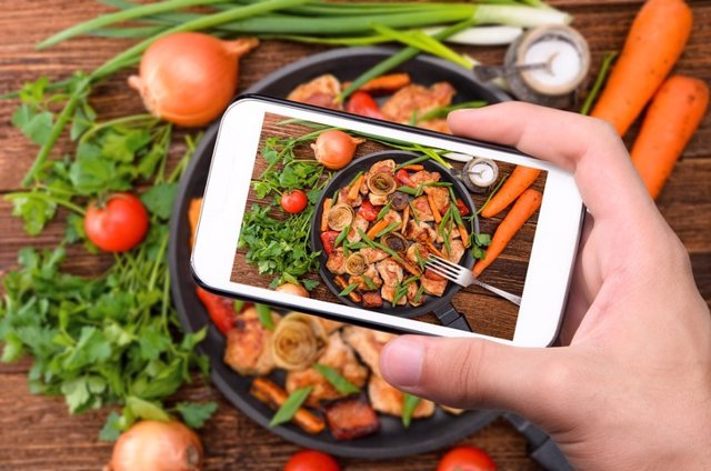 Hand using a smartphone to take photo of their meal