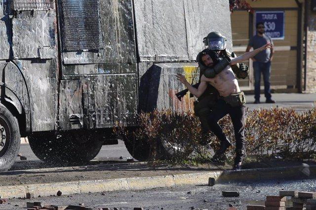 Un carabinero sujeta a un manifestante en el marco de la ola de protestas en Chile contra el Gobierno de Sebastián Piñera