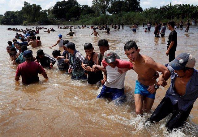 Grupo de migrantes centroamericanos cruzando un río a su paso por Ciudad Hidalgo, México.