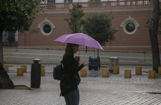 Una mujer se protege de la lluvia bajo su paragüas mientras camina. Sevilla.