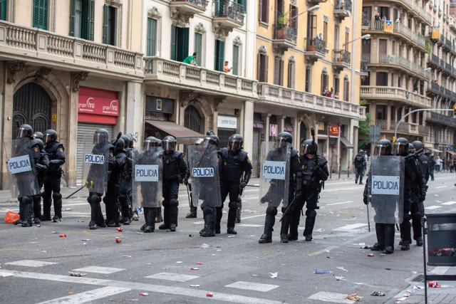 Agentes de la Policía Nacional forman una fila para cargar en la Vía Layetana durante la manifestación organizada por los sindicatos Intersindical-CSC e IAC en Barcelona.