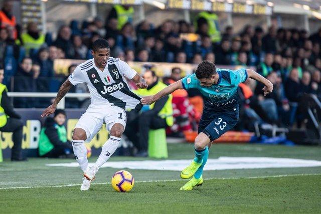 Douglas Costa pugna con Hateboer en el Atalanta-Juventus de la Serie A 2018-19