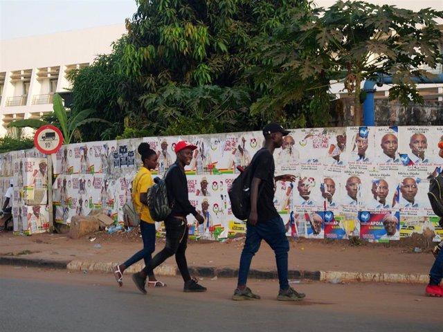 Personas caminando frente a un muro con carteles de la campaña presidencial en Bissau