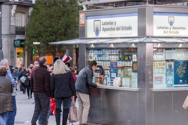 Varias personas esperan en cola para comprar un décimo de Lotería de Navidad en una Administración en la plaza de Puerta del Sol, en Madrid (España), a 18 de noviembre de 2019.