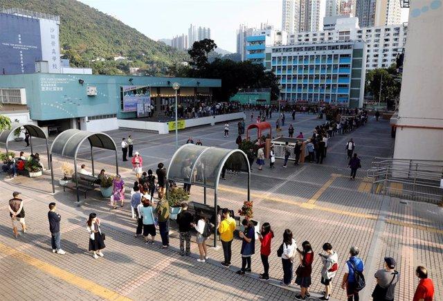 Electores hacen cola en un colegio electoral para votar en las elecciones municipales de Hong Kong de este domingo.