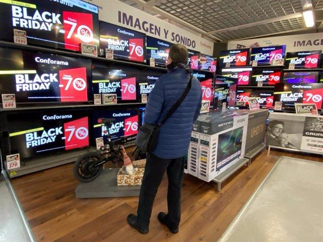Interior de una tienda de Conforama en la que un hombre mira varias pantallas en las que se anuncian descuentos de hasta el 70% en el Black Friday del próximo 29 de noviembre, en Madrid a 19 de noviembre de 2019.