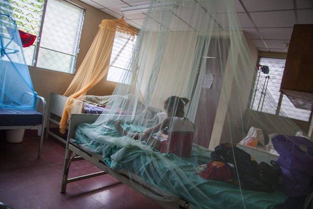 Una niña sentada en una cama con mosquitero en Nicaragua
