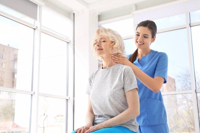 Mujer mayor recibiendo asistencia por una fisioterapeuta.