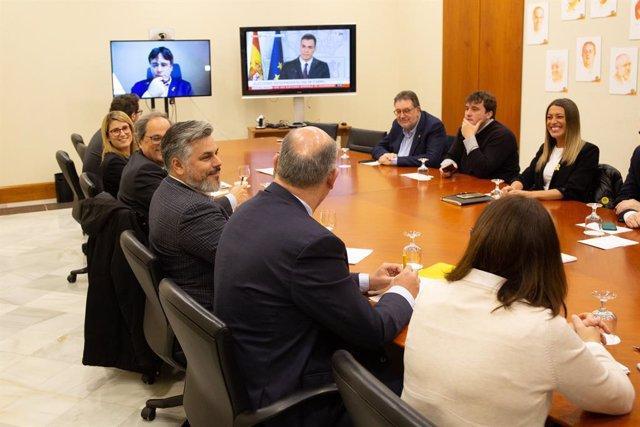 Els portaveus de Junts per Catalunya en el Parlament, Albert Batet, Quim Torra, Elsa Atardi i Pere Aragonès, entre altres portaveus del grup i del PDCat reunits (en pantalla amb Carles Puigdemont) veient la compareixença del president del Govern.