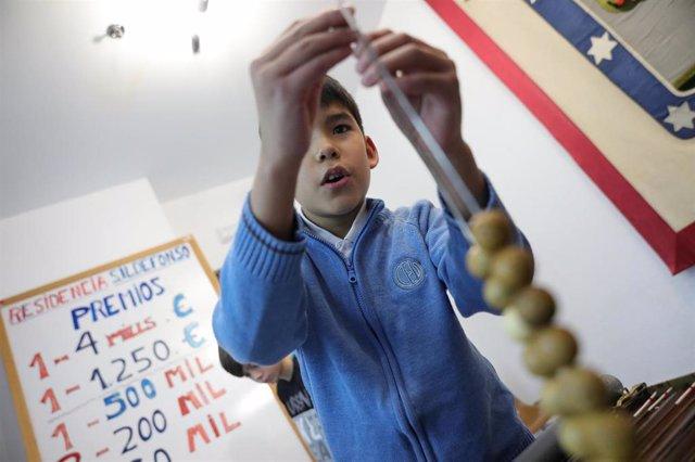 Un niño de la Residencia Internado San Ildefonso coloca números de la Lotería en un alambre, preparándose para la celebración del Sorteo de la Lotería de Navidad del próximo 22 de diciembre, en Madrid a 25 de noviembre de 2019.