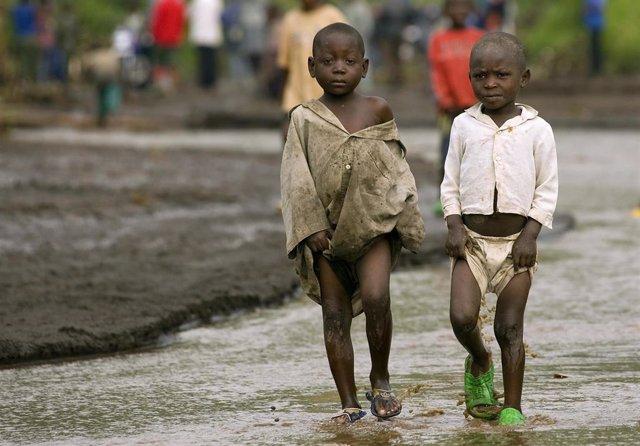 Dos niños pequeños caminan por una de las carreteras afectadas por las últimas inundaciones que ha sufrido la capital de la República Democrática del Congo, Kinsasa.